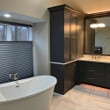 A master bathroom with a freestanding bathtub and a double sink with a large mirror above them. There are several cabinets to the left of the sinks and drawers underneath. The floors are a white and grey marbled porcelain and the walls are off-white.