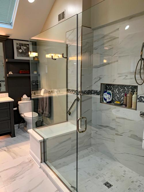 A large walk in shower with glass doors. The shower walls and floor are the same marbled porcelain tiling as the floors of the rest of the bathroom. There is a built in caddy to hold soap. There is also a seated area in the shower with a grab bar.