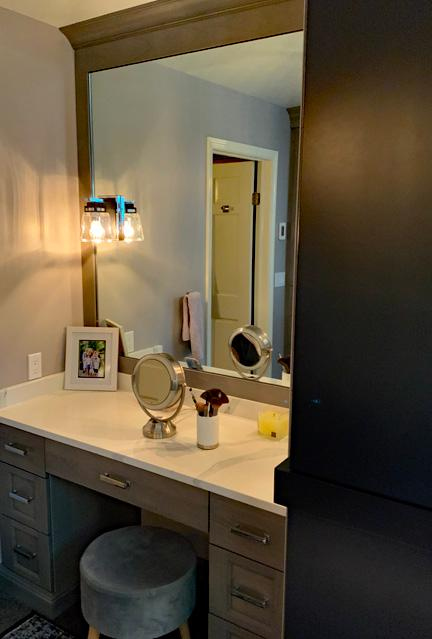 The make up area is a large vanity built in to the corner of the bathroom. There is a large mirror that extends to the ceiling. Underneath the vanity there are stacked drawers but there is also space in the middle where a stool sits.