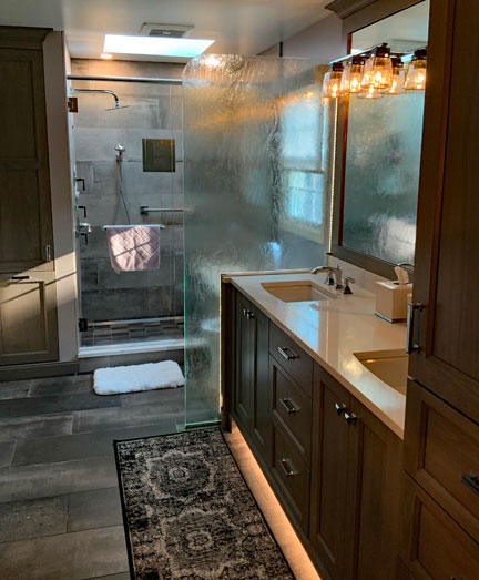 The right side of the same bathroom. There is a double sink with plenty of cabinet and drawer space underneath. Behind the sink is a fogged-glass partition which hides the commode. Behind that is the large walk-in shower that includes both a fixed and removable shower head and a grab bar. There is a skylight on the ceiling of the shower and the rightmost wall in the shower has a fogged glass window that let natural light into the room.